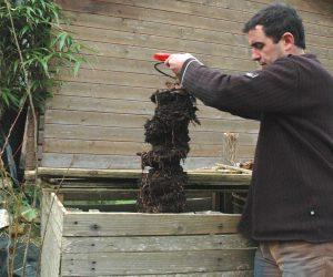 Manipulation de l'outil pour décompacter ou sortir le compost mûr.